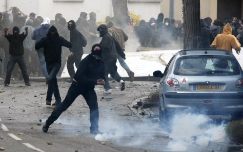 Image: Hooded anti-NATO demonstrators clash with French riot police