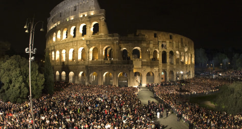 Image: The faithful attend the Via Crucis led by Pope Benedict XVI at the Colosseum in Rome
