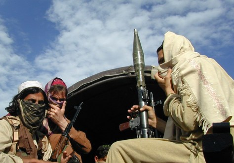 Image: Pakistani Taliban fighters sit with their weapons on the back of a truck in Buner