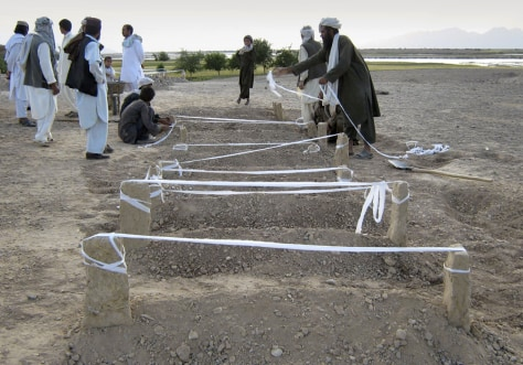 Image: Afghan villagers mark graves