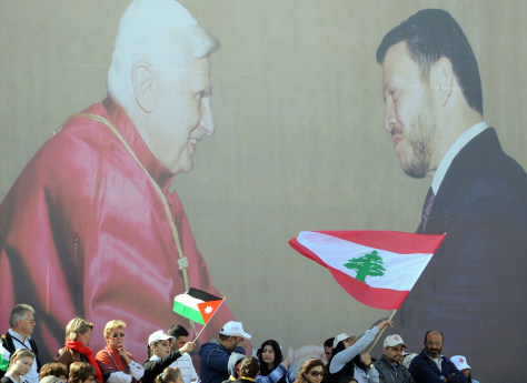 Image: Jordanian and Lebanese Christians wave national flags beneath a huge portrait of Pope Benedict XVI and Jordan's King Abdullah II