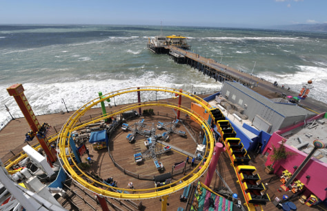Image: People enjoy riding a roller coaster at the Pacific Park in Santa Monica Pier, California