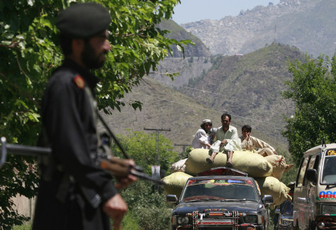 Image: Men fleeing a military offensive in Pakistan's Swat Valley