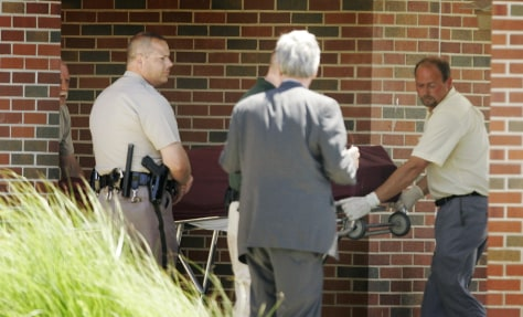 Image: The body of a shooting victim is removed from the Reformation Lutheran Church in Wichita, Kan.