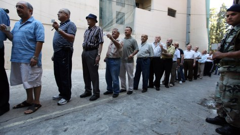 Image: Lebanese men line up at the entrance of a polling station
