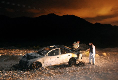 Image: Detectives investigate a burned-out Cadillac in the desert outside Las Vegas