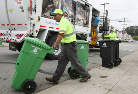 Image: Workers haul garbage cans