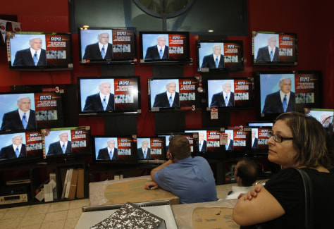 Image: Israeli shopper stands in front of televisions broadcasting the speech of Israel's Netanyahu in Jerusalem