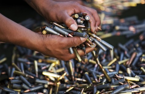 Image: A soldier picks up seized bullets