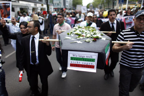 Image: Protesters carry a mock coffin and picture of a victim of violence in Tehran