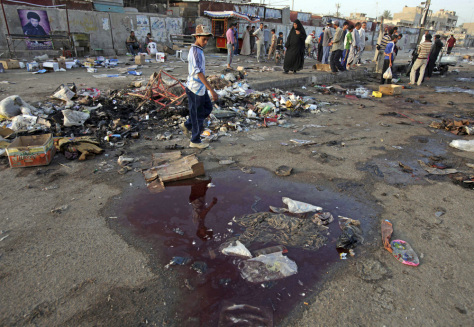 Image: Residents stand at the site of a bombing in the main Shiite district in Baghdad