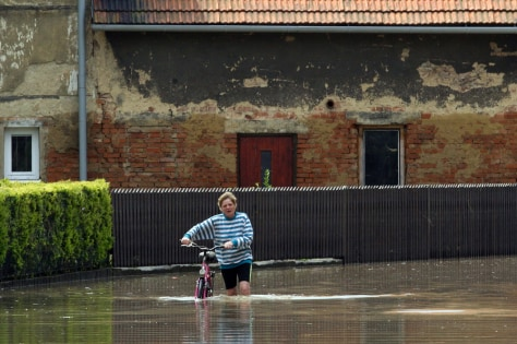 Image: Woman pushes bicycle through flooded Czech street
