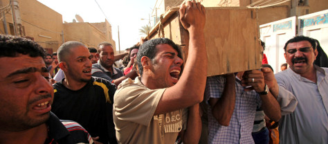 Image: Iraqi mourners carry a coffin