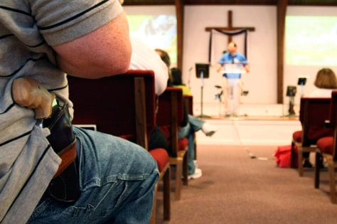 Image: A man with firearm listens to pastor Ken Pagano at the New Bethel Church in Louisville