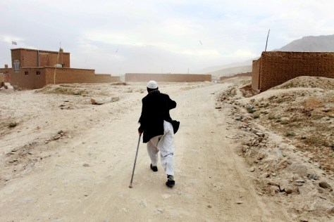 Image: Yosouf, 48, who lost a leg to a land mine while fighting against the Russian in Ghazni province, walks to his home