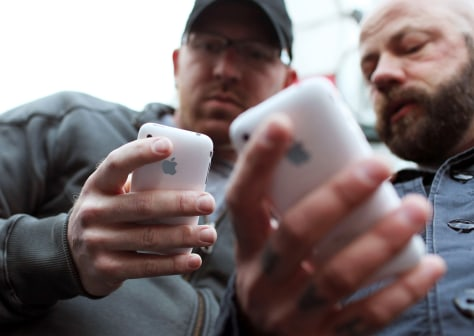 Image: Two men holding iPhones