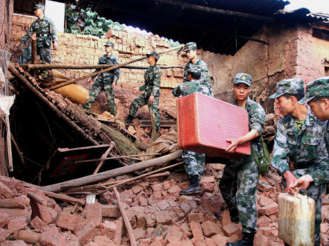 Image: Chinese soldiers collect belongings for residents at Guantun Village in China's Yunnan Province