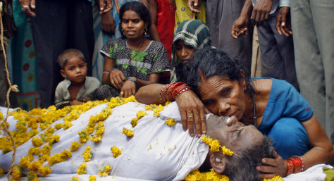 Image: A widow hugs the body of her late husband after he died for consuming spurious liquor in Ahmedabad, India.