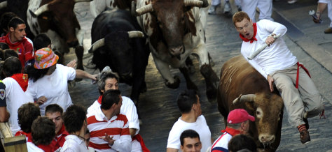 Image: A runner is tossed by a bull during the running of the bulls at the San Fermin festival in Pamplona