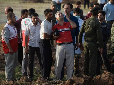Image: A relative grives at the Iran crash site