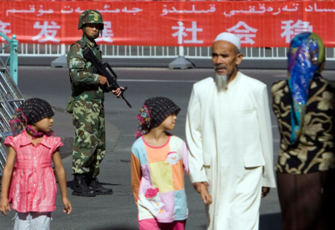 Image: Security forces and Uighur passersby.
