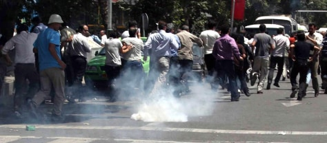 Image: Protesters run from tear gas in Tehran