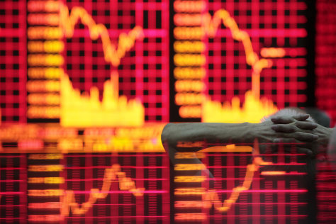 Image: A man reads information on an electronic screen at a brokerage house in Shanghai