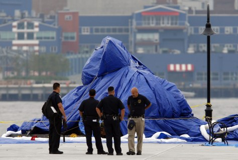 Image: Police stand guard in front of a helicopter wrapped in a blue tarp after it was recovered from the Hudson River, in Hoboken, N.J.