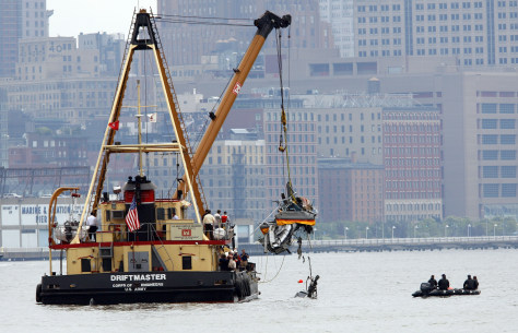 Image: Heavy lifting ship from U.S. Army Corps of Engineers lifts fuselage of helicopter from location of crash at Hudson River, in New York