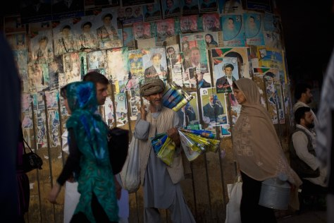 Image: Afghans walk past posters of provincial candidates