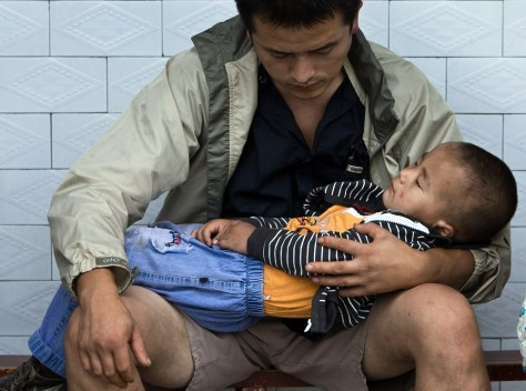 Image: A man holds his child while waiting for blood tests