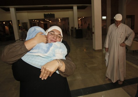 Image: Hadeel al-Shalchi,center face to camera, embraces a relative in Baghdad, Iraq.