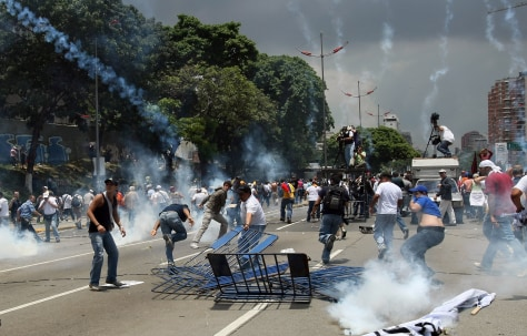 Image: Anti-Chavez protesters flee as riot police throw tear gas grenades at them