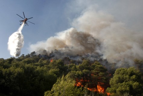 Image: A fire-fighting helicopter drops water over a forest fire in Nea Makri village northeast of Athens