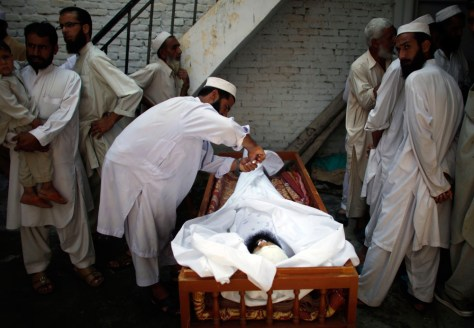 Image: Family members preparing to bury the body of alleged Taliban militant