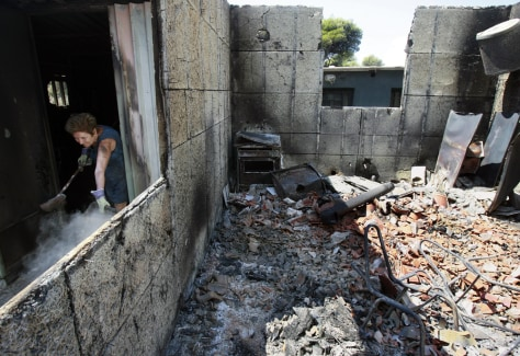 Image: Woman removes debris from damaged house in Penteli, Greece