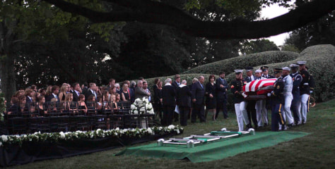Image: The Kennedy family gathers around the grave site as an Honor Guard carries the casket of Sen. Ted Kennedy at Arlington National Cemetery, in Arlington, Va.