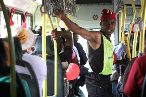 Image: A South African man holds on inside a Rea Vaya bus