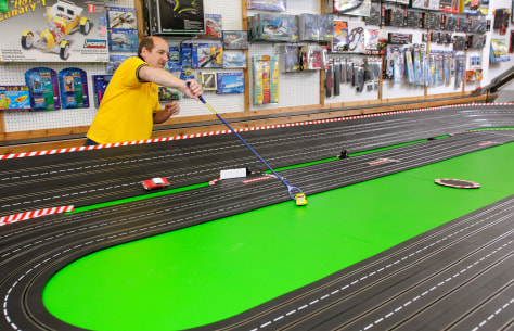 Image: Chris Fine of Mid-Hudson Hobbies reaches for a slot car