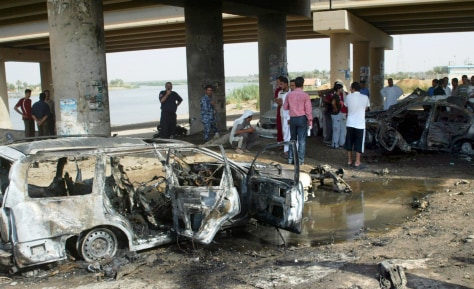 Image: Local residents look at destroyed vehicles after a car bomb attack in Ramadi