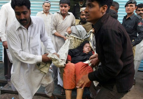 Image: A dead woman is removed from the scene of a stampede in Pakistan