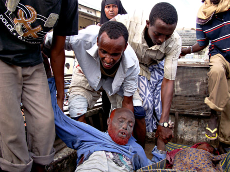 Image: Men attend to a wounded Somali man