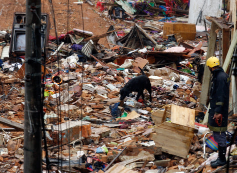 Image: Brazilian police sniffer dog searches for bodies at the site of collapsed houses in Santo Andre, on the outskirts of Sao Paolo