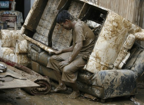 Image: A man takes a break from cleaning a house swamped by flash floods