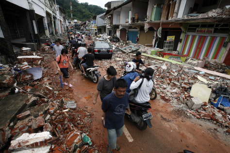 Image: Residents walk through an area damaged by an earthquake in Padang