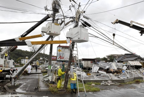 Image: Workers try to restore fallen power poles caused by Typhoon Melor in Japan