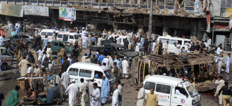 Image: Residents and security officials stand in the midst of the aftermath of a car-bomb explosion in Peshawar