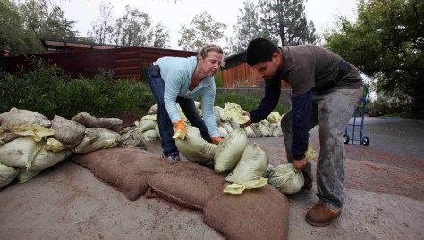 Image: People place sandbags in preparation for storm