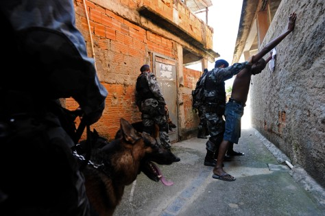 Image: Police frisk a man as they search for drugs and weapons in the Morro do Adeus slum