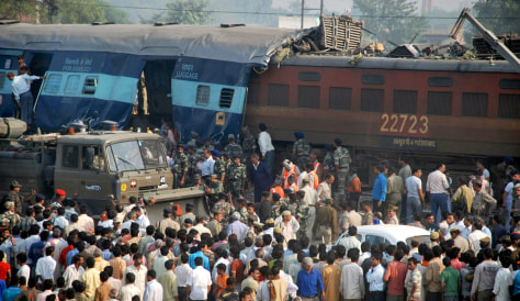 Image: Onlookers stand at site of train accident on the outskirts of Mathura.